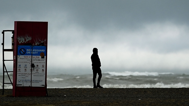 A man watches the waves roll in on Lake Ontario at Woodbine Beach on a windy day during the COVID-19 pandemic in Toronto on Wednesday, December 16, 2020. Toronto and Peel region continue to be in lockdown. THE CANADIAN PRESS/Nathan Denette