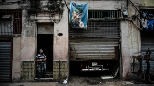 A man wearing a mask leaves his house where a picture of late leader Fidel Castro hangs on the wall in Havana, Cuba, on Jan. 11, 2021. (Ramon Espinosa / AP)