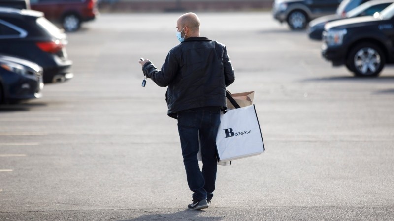 A shopper leaves Vaughan Mills Shopping Centre in Vaughan, Ontario, Sunday, Nov. 29, 2020. As malls in the Toronto core have shut due to provincial orders, shoppers flocked to malls on the outskirts of the Greater Toronto Area for Black Friday weekend shopping. THE CANADIAN PRESS/ Cole Burston