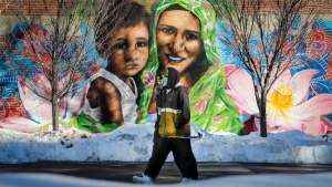 A couple wearing masks walk past a mural of a mother and child in Calgary, Alta., Monday, Dec. 28, 2020, amid a worldwide COVID-19 pandemic. (THE CANADIAN PRESS / Jeff McIntosh)