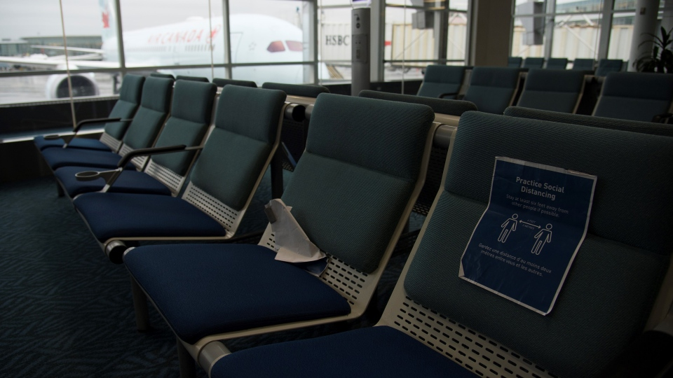 A plane is seen through the window on the tarmac of Vancouver International Airport as the waiting room is empty Tuesday, June 9, 2020. (Jonathan Hayward / THE CANADIAN PRESS)