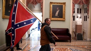 Kevin Seefried carries a Confederate battle flag on the second floor of the U.S. Capitol after breaching security defenses, on Jan. 6, 2021. (Mike Theiler/Reuters/CNN)