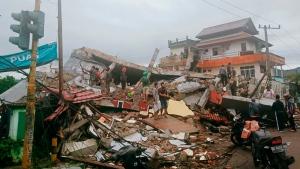 Residents inspect earthquake-damaged buildings in Mamuju, West Sulawesi, Indonesia, Friday, Jan. 15, 2021. (AP Photo/Rudy Akdyaksyah)