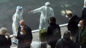 Members of the World Health Organization (WHO) investigative team are directed by a worker in protective gear after arriving at the airport in Wuhan, China on Thursday, Jan. 14, 2021.