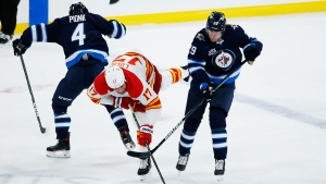 Calgary Flames' Milan Lucic (17) gets checked by Winnipeg Jets' Neal Pionk (4) as Patrik Laine (29) looks for the puck during opening game second period NHL action in Winnipeg, Thursday, Jan. 14, 2021. THE CANADIAN PRESS/John Woods