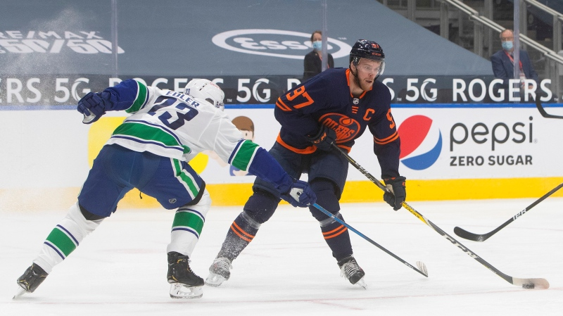 Edmonton Oilers' Connor McDavid (97) makes a move to get past Vancouver Canucks' Alexander Edler (23) during second period NHL action in Edmonton on Thursday, January 14, 2021. THE CANADIAN PRESS/Jason Franson