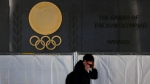 A man wearing a face mask to protect against the spread of the coronavirus walks along the Japan National Stadium, where opening ceremony and many other events are planned for Tokyo 2020 Olympics, as engravings in honor of 1964 Tokyo Olympics are seen on the side of the stadium wall behind the fence Wednesday, Jan. 13, 2021, in Tokyo. (AP Photo/Kiichiro Sato)
