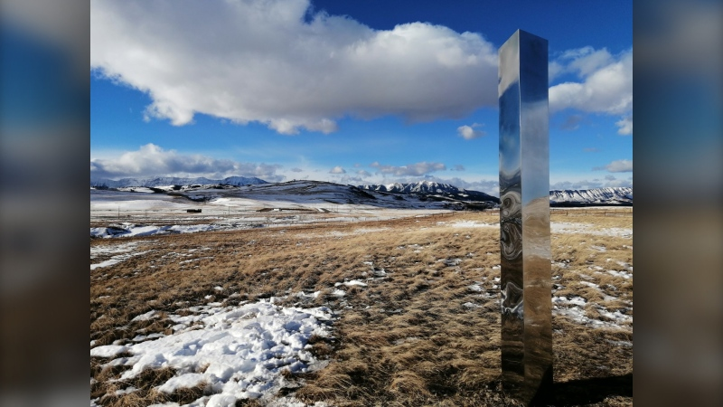 A monolith in Alberta is shown in a recent handout photo. A tall, stainless steel beacon that has been placed along the eastern slopes of the Alberta Rockies comes with a message. The three-metre monolith, which reflects its surroundings, is one of many that have been found at sites around the world. (THE CANADIAN PRESS/HO-Elizabeth Williams)