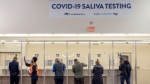 People get tested at the new saliva COVID-19 testing site at the Minneapolis-St. Paul International Airport, Thursday, Nov. 12, 2020. The airport partnered with the Minnesota Department of Health (MDH), Vault Medical Services and the Metropolitan Airports Commission (MAC) to open its ninth COVID-19 PCR saliva testing location. It is free to Minnesota residents and out-of-state residents. (Elizabeth Flores/Star Tribune via AP)