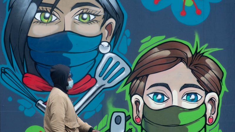 A man walks past a mural in downtown Ottawa Thursday January 14, 2021. (Adrian Wyld/THE CANADIAN PRESS)