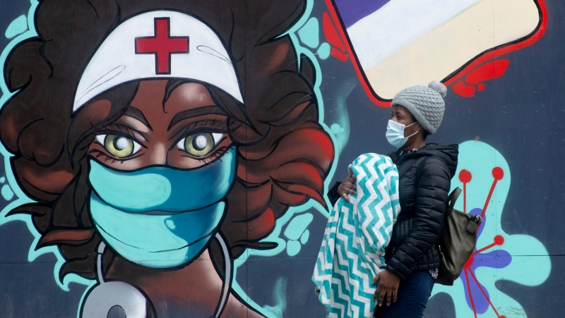A woman walks past a mural in downtown Ottawa, Thursday January 14, 2021 in Ottawa. (Adrian Wyld/THE CANADIAN PRESS)