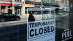 Storefronts in Ottawa's Glebe neighbourhood are reflected in a sign indicating the temporary closure of a business to prevent the spread of COVID-19, on Tuesday, March 24, 2020. THE CANADIAN PRESS/Justin Tang