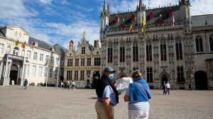 A couple in protective face masks consult a tourist map in the center of Bruges, Belgium, Monday, Aug. 24, 2020. (AP Photo/Virginia Mayo)