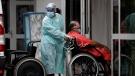A health worker wheels a patient suspected of having COVID-19 into the HRAN Hospital in Brasilia, Brazil, Thursday, Jan. 14, 2021. (AP Photo/Eraldo Peres)