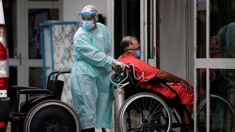 A health worker wheels a patient suspected of having COVID-19 into the HRAN Hospital in Brasilia, Brazil, Thursday, Jan. 14, 2021. (AP Photo/Eraldo Peres)