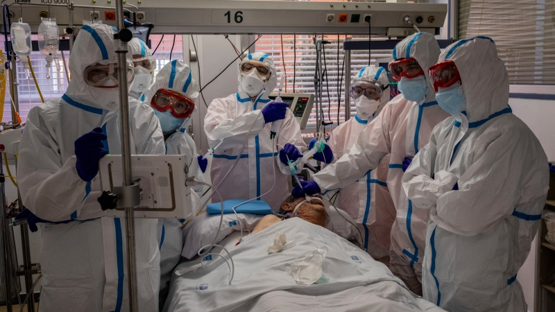 A patient infected with COVID-19 is treated in one of the intensive care units (ICU) at the Severo Ochoa hospital in Leganes, outskirts of Madrid, Spain, Friday, Oct. 9, 2020. (AP Photo/Bernat Armangue)