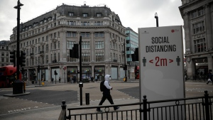 A man wearing a face mask to curb the spread of coronavirus walks past a social distancing sign at Oxford Circus in London, Friday, Jan. 15, 2021, during England's third national lockdown since the coronavirus outbreak began. The U.K. is under an indefinite national lockdown to curb the spread of the new variant, with nonessential shops, gyms and hairdressers closed, most people working from home and schools largely offering remote learning. (AP Photo/Matt Dunham)