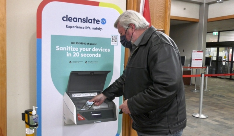 Dave Dayment, manger of the Timmins Victor M. Power Airport, places his cellphone and other pocket items in a new sanitizing machine on loan from its manufacturer. The unit helps prevent COVID-19 and other viruses from catching a free flight. (Lydia Chubak/CTV News)