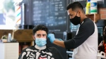 David Dzul, owner of Barber HQ, styles Jonathan Ruiz's hair Tuesday, July 7, 2020, in Yakima, Wash. The barber shop reopened Monday after four months of closure because of the coronavirus pandemic. (Amanda Ray/Yakima Herald-Republic via AP)
