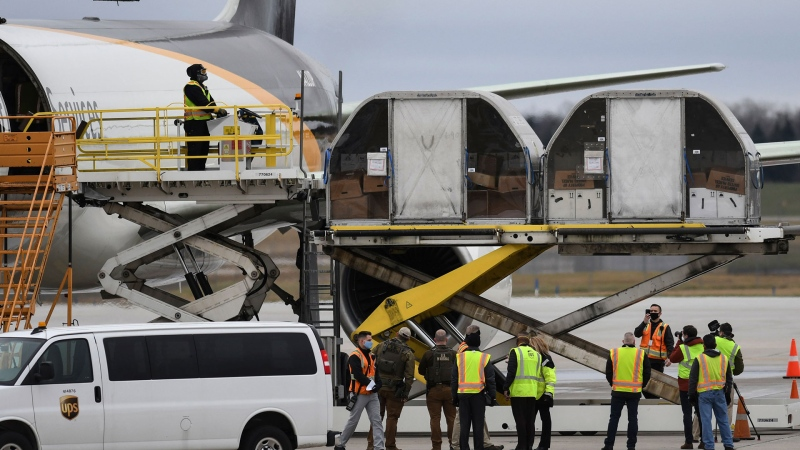 The first shipment of the Pfizer-BioNTech COVID-19 vaccine is loaded onto a UPS jet Sunday, Dec. 13, 2020, at Michigan's UPS hub at Capital Region International Airport in Lansing, Mich. (Matthew Dae Smith/Lansing State Journal via AP)