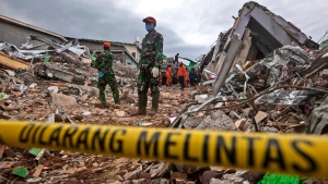 Rescuers search for victims at the ruin of a building flattened during an earthquake in Mamuju, West Sulawesi, Indonesia, Saturday, Jan. 16, 2021. Damaged roads and bridges, power blackouts and lack of heavy equipment on Saturday hampered Indonesia's rescuers after a strong and shallow earthquake left a number of people dead and injured on Sulawesi island. (AP Photo/Yusuf Wahil)