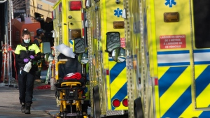 A paramedic walks past a row of ambulances after transporting a patient Friday, January 15, 2021 in Montreal. THE CANADIAN PRESS/Ryan Remiorz