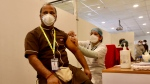 A health worker, left, receives a COVID-19 vaccine at a private Hospital in New Delhi, India, Saturday, Jan. 16, 2021. (AP Photo/Manish Swarup)