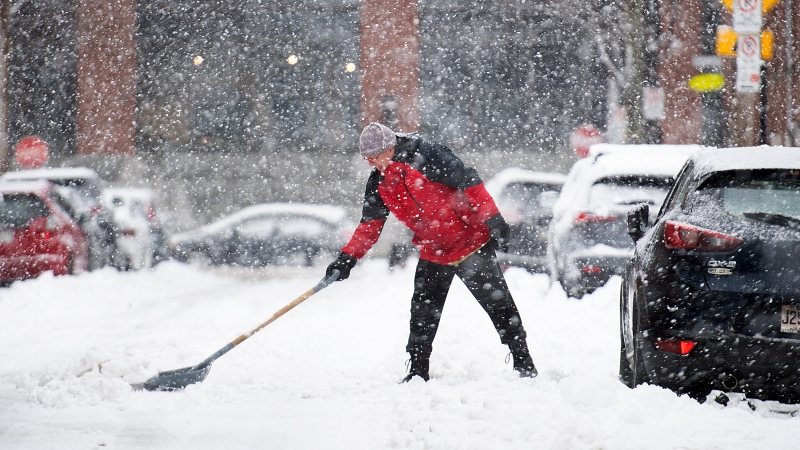 A man clears snow from around his car during a snowstorm in Montreal on Saturday January 16, 2021. THE CANADIAN PRESS/Graham Hughes