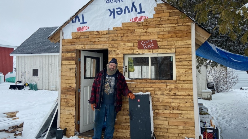 Guy Lamarche stands outside his 'bunkie' in Carp. The 64-year-old built it himself using items destined for landfills. (Dylan Dyson / CTV News Ottawa)