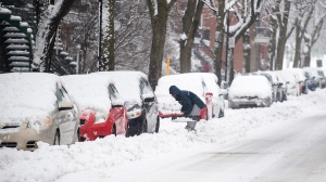 A person shovels snow from around a car during a snowstorm in Montreal, Saturday, January 16, 2021. THE CANADIAN PRESS/Graham Hughes