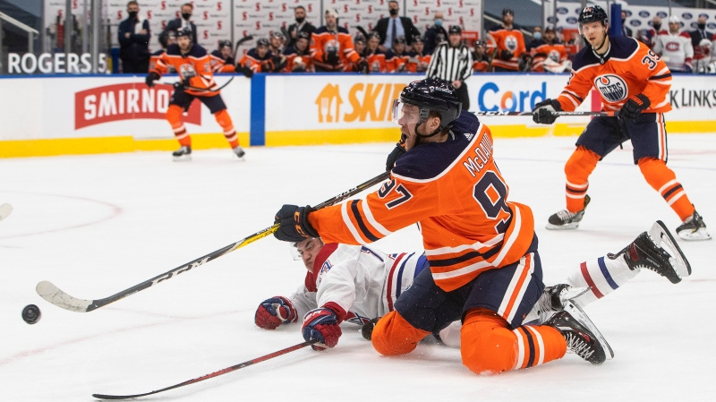 Edmonton Oilers' Connor McDavid (97) gets the shot away as Montreal Canadiens' Nick Suzuki (14) defends during second period NHL action in Edmonton on Saturday, January 16, 2021. THE CANADIAN PRESS/Jason Franson