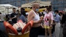 In this file photo, a local resident tries out ice-cream crepe at a weekend open air market in Beijing on Saturday, Aug. 8, 2020. (AP Photo/Ng Han Guan)