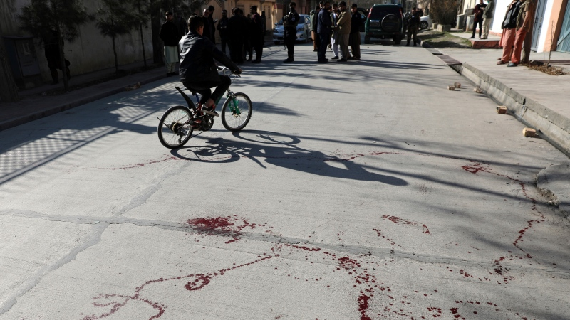 Blood stains the ground at the scene where gunmen fired in Kabul, Afghanistan, Sunday, Jan. 17, 2021. (AP Photo/Rahmat Gul)