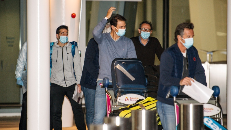 Spain's Rafael Nadal, center, arrives at Adelaide Airport ahead of the Australian Open tennis championship, Adelaide, Australia, Thursday, Jan. 14, 2021. (Morgan Sette/AAP Image via AP)