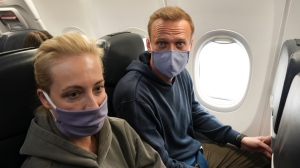Alexei Navalny and his wife Yulia sit in the plane prior to flight to Moscow in the Airport Berlin Brandenburg (BER) in Schoenefeld, near Berlin, Germany, Sunday, Jan. 17, 2021. (AP Photo/Mstyslav Chernov)