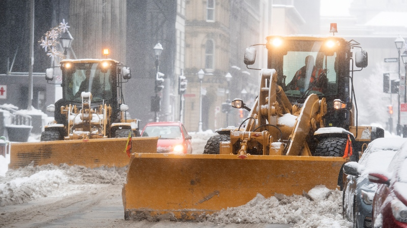 Plows clear snow from a street during a snowstorm in Montreal, Saturday, January 16, 2021. THE CANADIAN PRESS/Graham Hughes