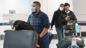 Passengers are shown in the international arrivals hall at Montreal-Trudeau Airport in Montreal, Tuesday, December 29, 2020, as the COVID-19 pandemic continues in Canada and around the world. The government of Quebec has asked that passengers be tested for COVID-19 prior to boarding flights bound for and on arrival at international airports in the province. THE CANADIAN PRESS/Graham Hughes