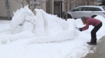 Dr. Mary Naciuk, a family doctor in south Ottawa, uses a blowtorch to touch up her sculpted snow dragon on her front lawn. Jan. 17, 2021 (Mike Mersereau / CTV News Ottawa)