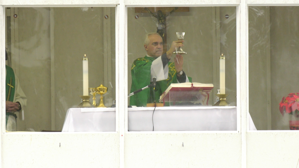 Father Gerard Monaghan delivers a sermon behind glass while parishioners remain in their cars, tuning in over using the FM radios. (Shaun Vardon / CTV News Ottawa)