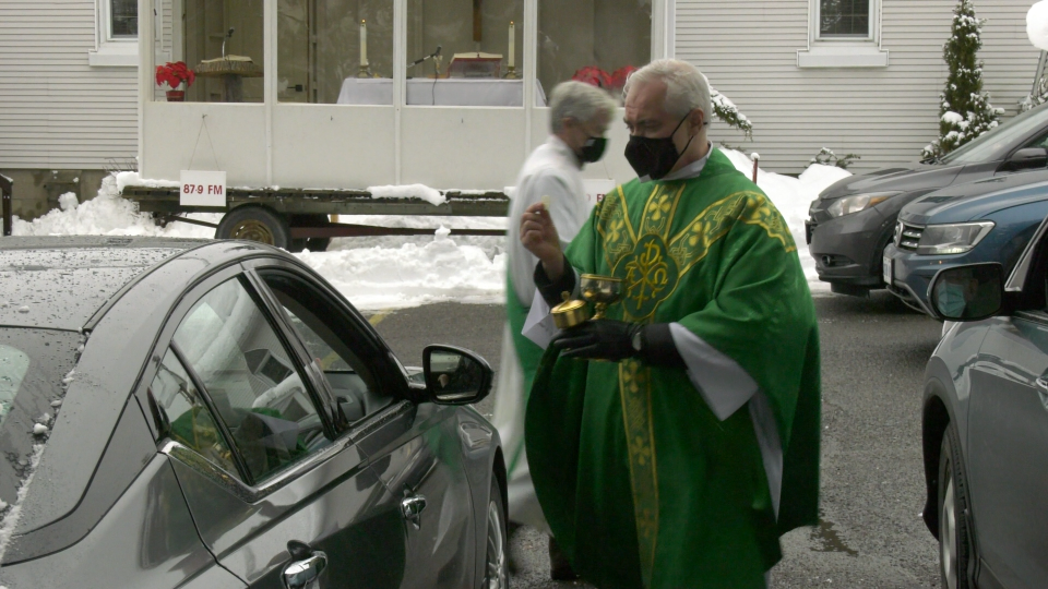Father Gerard Monaghan delivers the Eucharist to a parishioner of St. Faustina Parish in Cumberland, Ont. during a drive-in service. (Shaun Vardon / CTV News Ottawa)