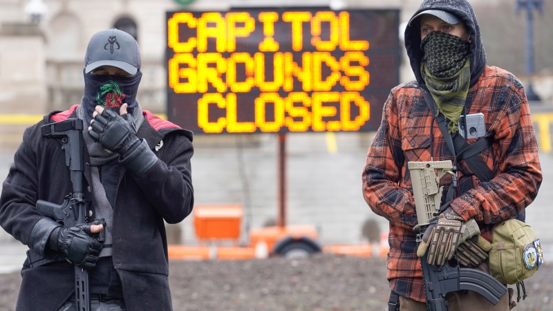 Members of the Boogaloo Boys, holding semi-automatic weapons stand outside at the Capitol building in Frankfort, Ky., Wednesday, Jan 17, 2021. (AP Photo/Bryan Woolston)