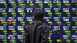 A man looks at an electronic stock board at a securities firm in Tokyo Friday, Jan. 15, 2021. (AP Photo/Eugene Hoshiko)