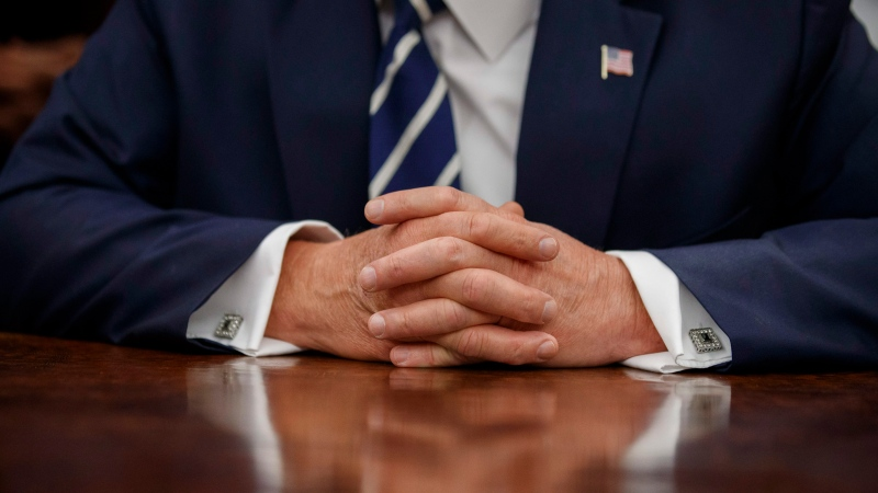 The hands of U.S. President Donald Trump are folded on the Resolute desk during a photo opportunity commemorating the 50th anniversary of the Apollo 11 moon landing, in the Oval Office of the White House, Friday, July 19, 2019, in Washington. (AP Photo/Alex Brandon)