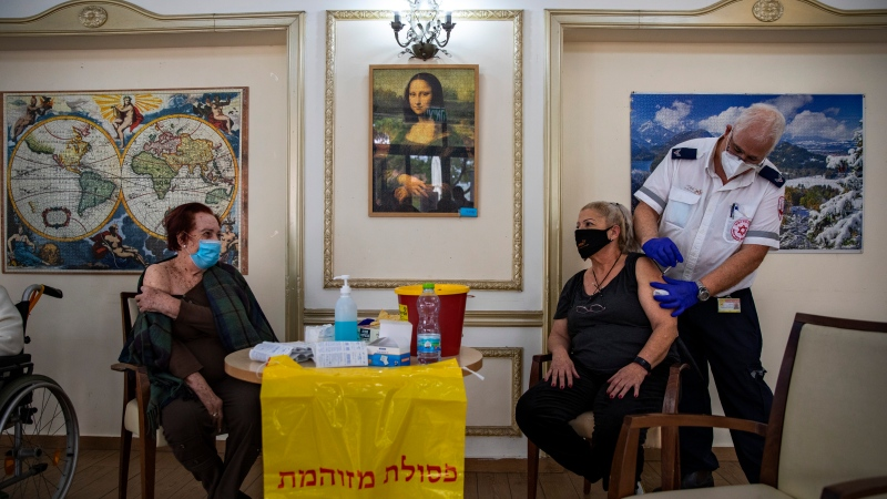 An Israeli woman receives the second Pfizer-BioNTech COVID-19 vaccine from a Magen David Adom national emergency service volunteer, at a private nursing home, in Ramat Gan, Israel, during a nationwide lockdown to curb the spread of the virus, Wednesday, Jan. 13, 2021. (AP Photo/Oded Balilty)