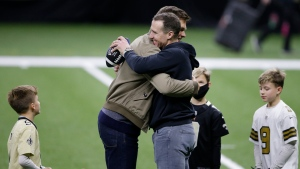 New Orleans Saints quarterback Drew Brees right, embraces Tampa Bay Buccaneers quarterback Tom Brady as Bree's children look on after an NFL divisional round playoff football game between the New Orleans Saints and the Tampa Bay Buccaneers, Sunday, Jan. 17, 2021, in New Orleans. (AP Photo/Butch Dill)