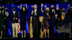 US President-elect Joe Biden (C) with his wife Jill Biden and members of their family salute the crowd on stage after delivering remarks in Wilmington, Delaware, on November 7, 2020. (AFP)