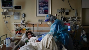 Registered nurse Merri Lynn Anderson, right, tends to her patient in a COVID-19 unit at St. Joseph Hospital in Orange, Calif., Thursday, Jan. 7, 2021. (AP Photo/Jae C. Hong)