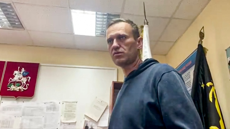 In this image taken from video released by @Kira_Yarmysh, Russian opposition leader Alexei Navalny gestures as he waits for a court hearing in a police station in Khimki, outside in Moscow, Russia, Monday, Jan. 18, 2021. Russian opposition leader Alexei Navalny's arrest as he arrived in Moscow after recovering from his poisoning with a nerve agent has drawn widespread criticism from Western nations. (@Kira_Yarmysh via AP)