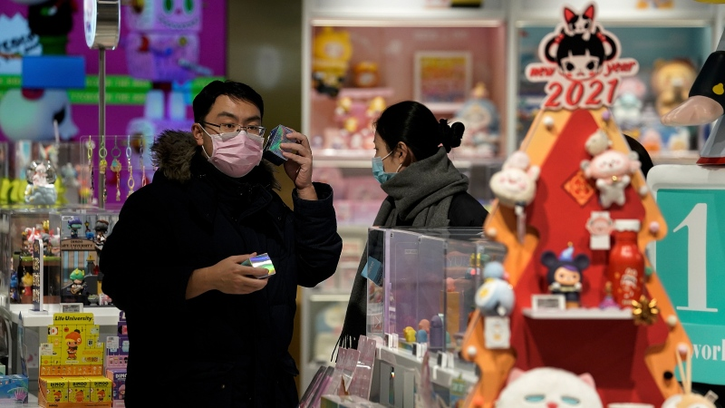 A man wearing a face mask to help curb the spread of the coronavirus shakes a toy box at the Chinese toy maker POP Mart in Beijing, Monday, Jan. 18, 2021. (AP Photo/Andy Wong)