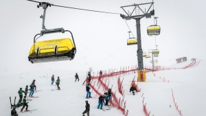 Volunteers work on the ski slope, in St. Moritz, Switzerland, Saturday, December 5, 2020. (Jean-Christophe Bott/Keystone via AP)
